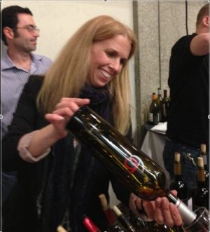 Debra Sommerfield pouring wine at Unified Symposium