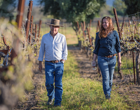 Bernie Luchsinger and Pilar Luchsinger White walking in vineyard