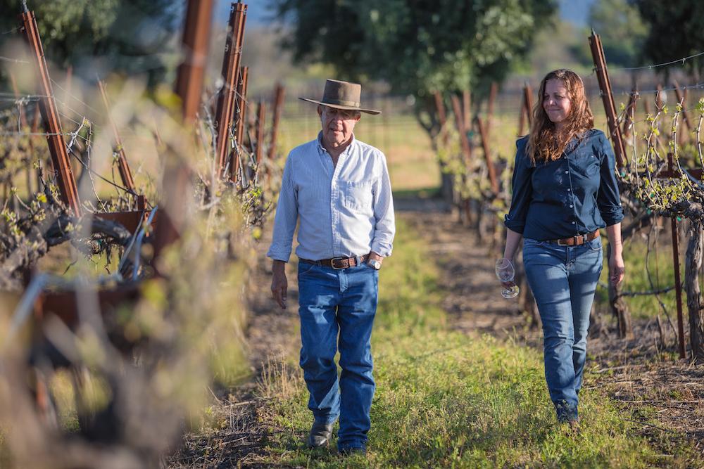 Bernie Luchsinger and Pilar Luchsinger White walking in vineyard