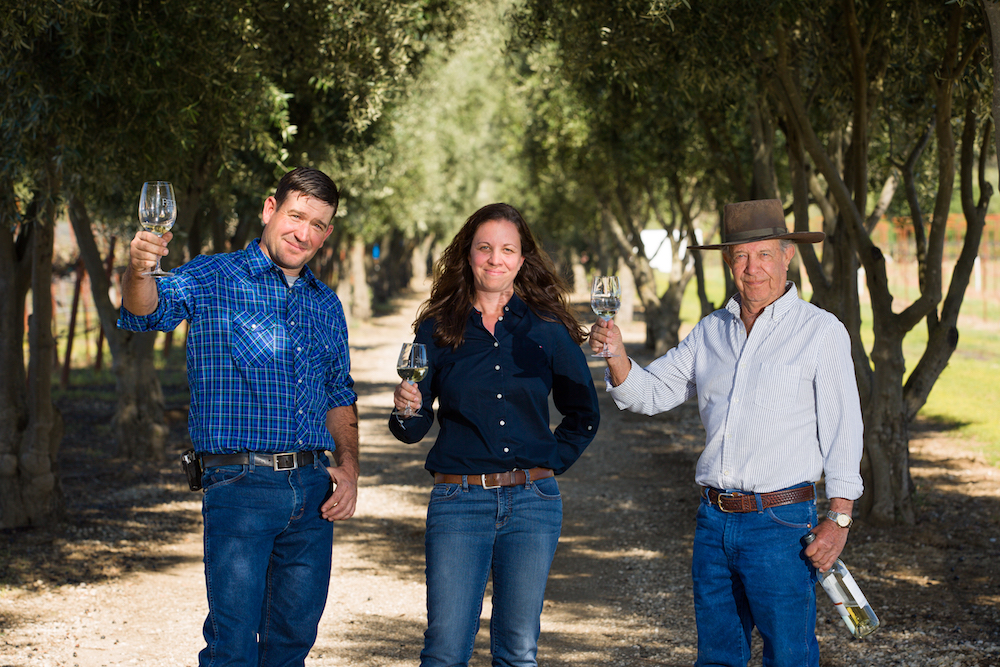 Ryan White, Pilar Luchsinger White, and Bernie Luchsinger standing on tree lined path with wine glasses