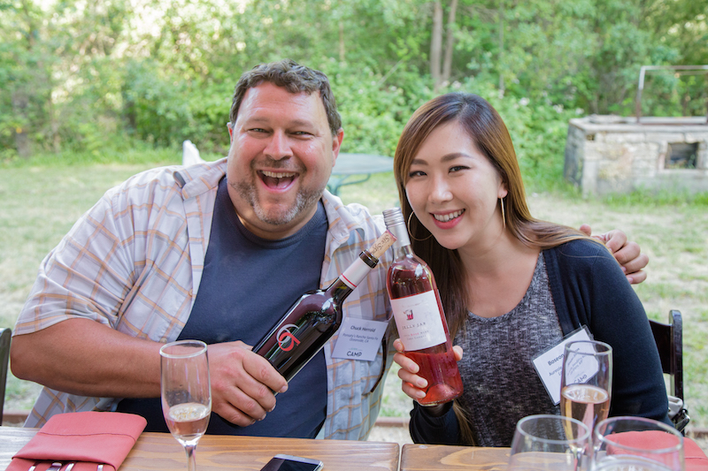 Two SOMM Camp attendees with bottles of wine