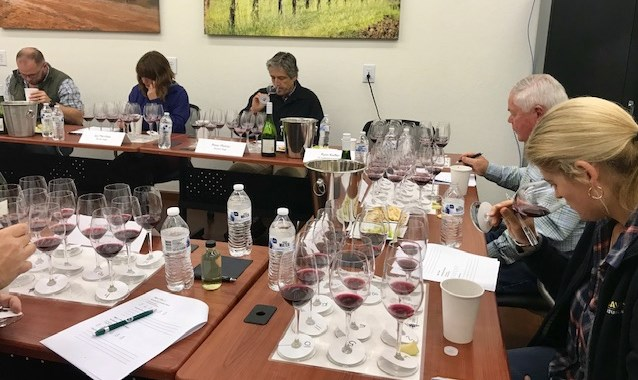 Sensory Analyst Tasting group analyzing and recording findings of impacted wines