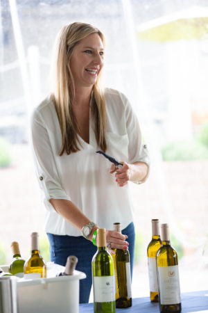 Woman opening wine bottle at Sauvignon Blanc Experience event